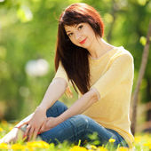 Young woman in the park with flowers — Stock Photo