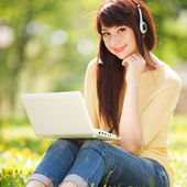 Cute woman in earphones with white laptop in the park — Stock Photo