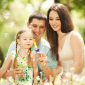 Happy mother, father and daughter blowing bubbles in the park — Stock Photo