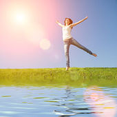 Pretty young woman jumping on green grass — Stock Photo