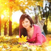 Giovane bella donna resto nel parco d'autunno — Foto Stock