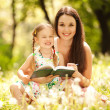 Mother and daughter drawing on grass in park — Stock Photo #14183357