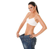 Funny woman shows her weight loss by wearing an old jeans, isola — Stock Photo