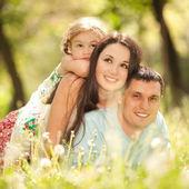 Gelukkig moeder, vader en dochter in het park — Stockfoto