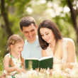 Happy mother, father and daughter read a book in the park — Stock Photo #14529833
