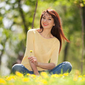 Young happy woman in the park with flowers — Stock Photo