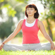 Pretty woman meditate in the park — Stock Photo
