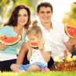 Happy family having picnic in green garden — Stock Photo #14975087