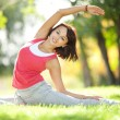 Pretty woman doing yoga exercises in the park — Stock Photo #14975091