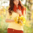 Young pretty woman walking in the autumn park — Stock Photo #14975263