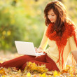 Cute woman with white laptop in the autumn park — Foto Stock