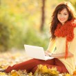Cute woman with white laptop in the autumn park — ストック写真