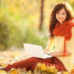 秋の公園で白いラップトップとかわいい女 — ストック写真