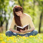 若い女性の花の公園で本を読んで — ストック写真