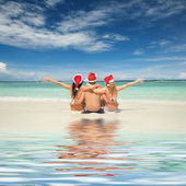 Happy friends in santa hats on the beach. Christmas vacation — Stockfoto