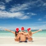 Happy friends in santa hats on the beach. Christmas vacation — Stock Photo