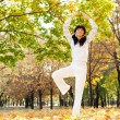 Pretty woman doing yoga exercises in the autumn park — Stock Photo #15217805