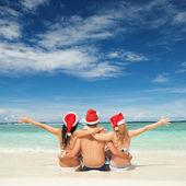 Amigos felizes em chapéus de papai noel na praia. férias de natal — Foto Stock