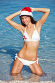 Happy santa woman on the beach. Christmas vacation — 图库照片