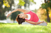 симпатичная женщина делает йога упражнения в парке — Стоковое фото