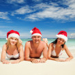 Happy friends in santa hats on the beach. Christmas vacation — Stock Photo #16177681