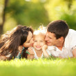 Happy mother and father kissing their daughter in the park — Stock Photo #16177737