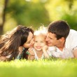 Happy mother and father kissing their daughter in the park - Stock Photo