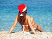 Young woman in santa hat sitting on the beach. Christmas vacatio — Stock Photo