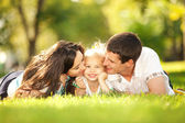 Happy mother and father kissing their daughter in the park — Stok fotoğraf