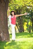 Pretty woman doing sports exercises in the park — Stock Photo