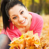 Fun pretty woman playing in the autumn park — Stock Photo