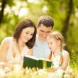 Happy mother, father and daughter read a book in the park — Stock Photo #16496289