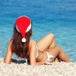Young woman in santa hat sitting on the beach. Christmas vacation — Stock Photo #16496337