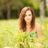Young redhead woman in the park with flowers — Stock Photo