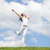 Mooie jonge vrouw springen op groen gras — Stockfoto