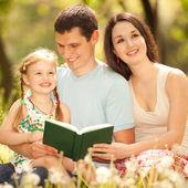 幸せな母、父および娘は公園で本を読む — ストック写真