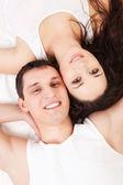 Beyaz yatakta yatan genç mutlu çift — Stok fotoğraf