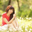Cute woman in the park with dandelions — Stock Photo #17343463
