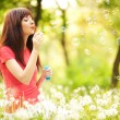 Happy woman blowing bubbles in the park — Stock Photo #17343465