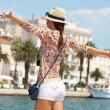 Happy young woman with outstretched hand and see on old town — Stock Photo