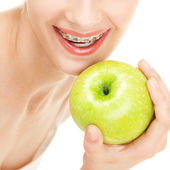 Girl in braces with green apple on white background — Stock Photo