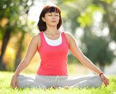 Pretty woman meditate in the park — Stock Photo