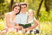 Happy mother, father and daughter read a book in the park — Stockfoto