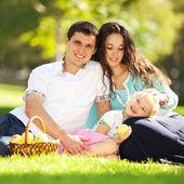 Happy family having a picnic in the green garden — Stock Photo