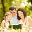 Happy mother, father and daughter read a book in the park — Stock fotografie