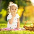Cute little girl eating apple in the park — Stock Photo #17591801