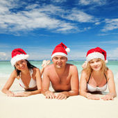 Happy friends in santa hats on the beach. Christmas vacation Stock Image