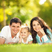 Happy mother, father and daughter in the park — Stockfoto