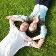 Stock Photo: Happy couple relaxing on green grass