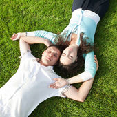 Happy couple relaxing on green grass — Stock Photo
